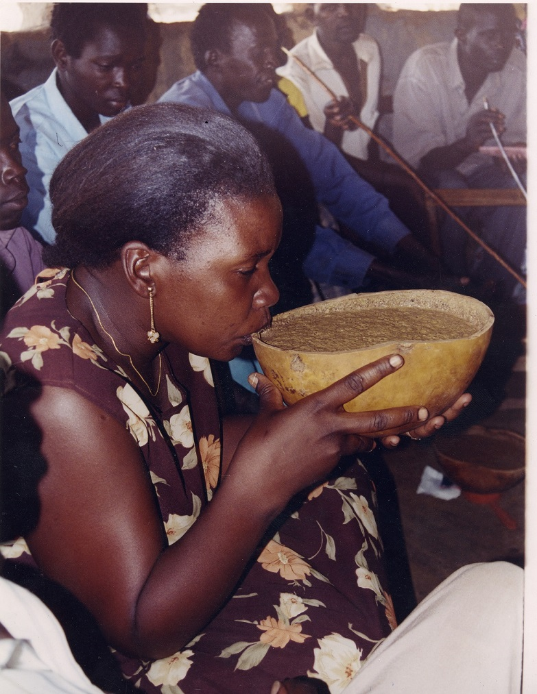 A lady sips on Malwa from a calabash called Adere in Teso