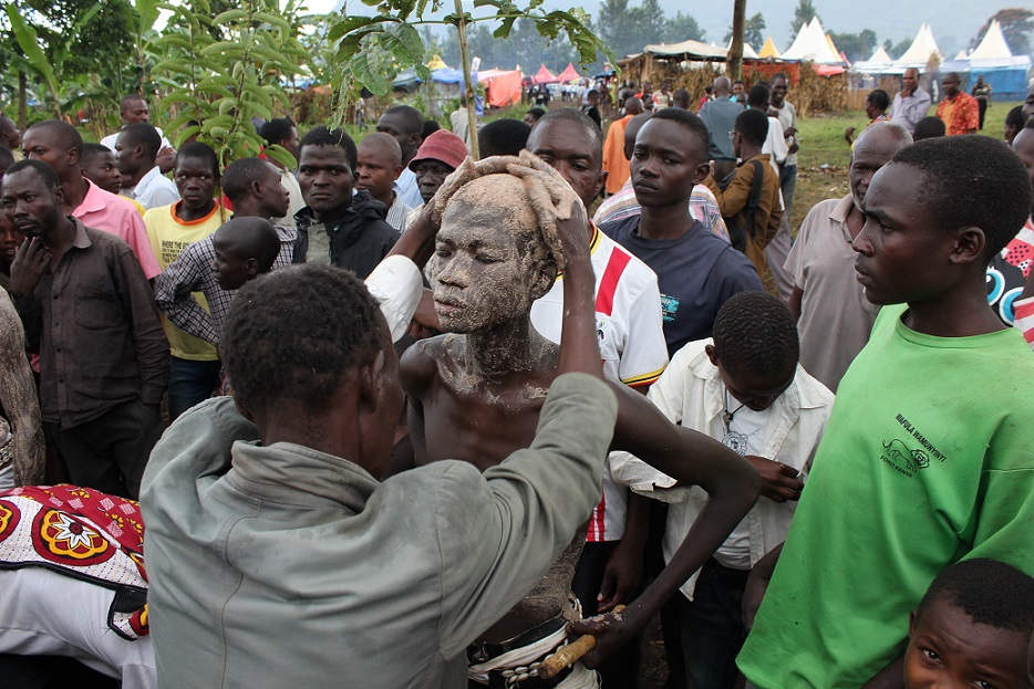 Gidudu gets smeared with thick millet yeast paste on the first day of the three day Imbalu rituals