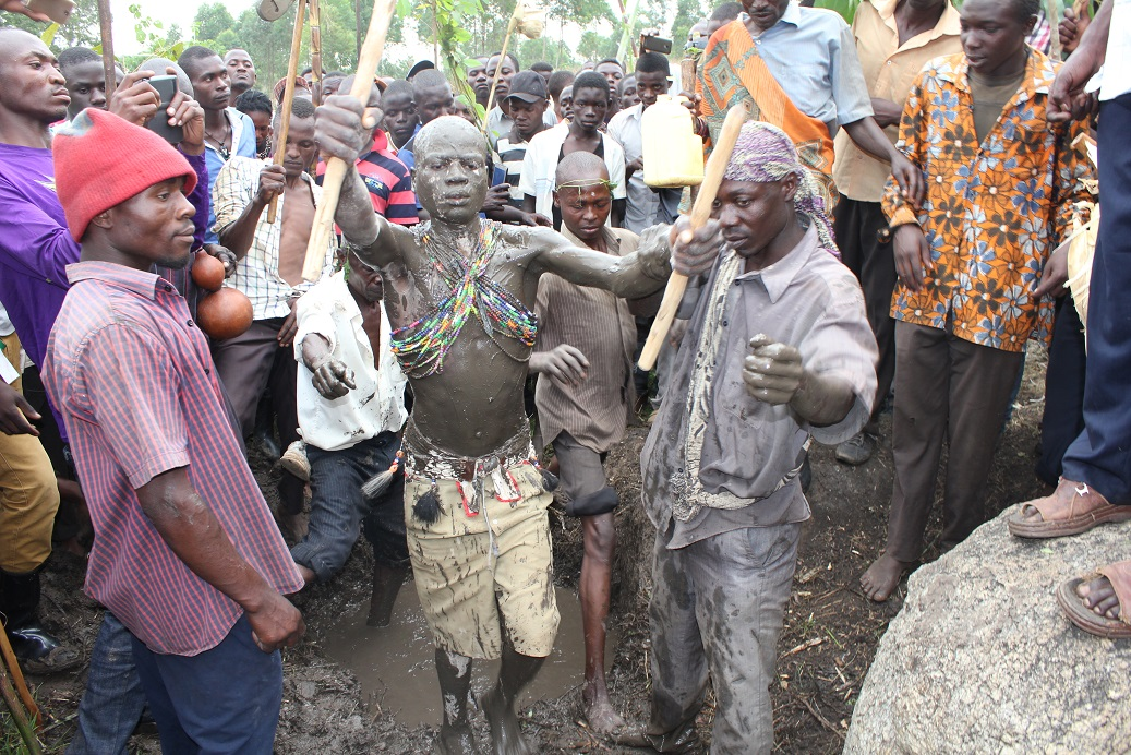 Khabeli is led away from the Black mud swamp after he had been smeared