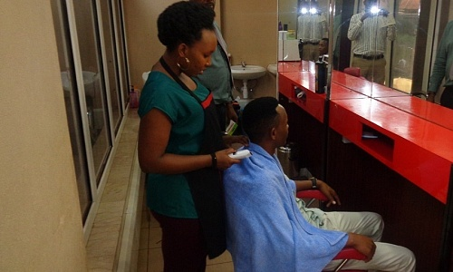 A man gets his hair cut in one of Kampala's many unisex salons