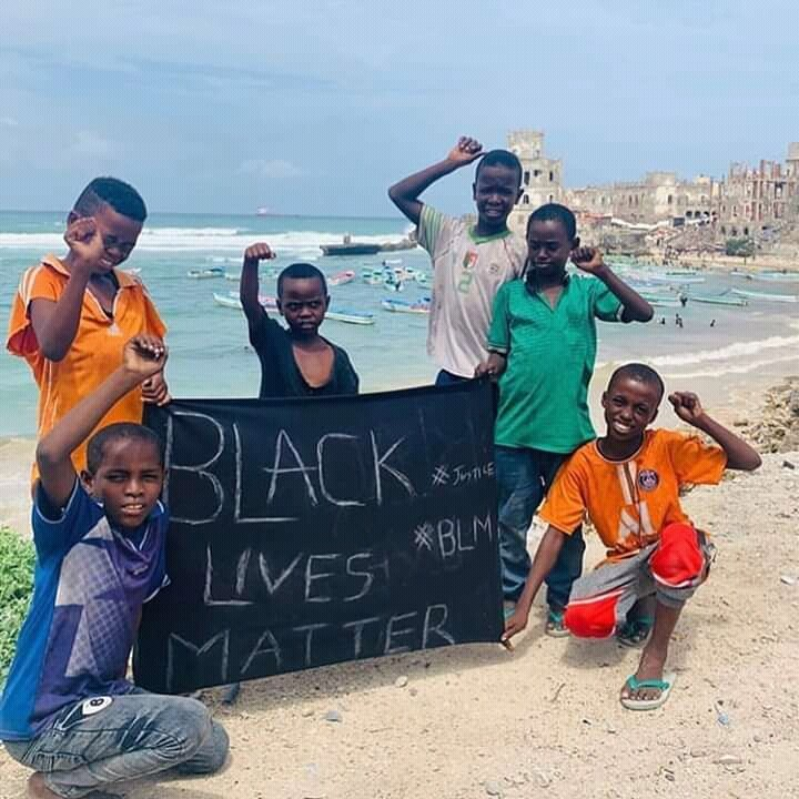 Somali children holding a cloth emblazoned with the words- Black Lives Matter
